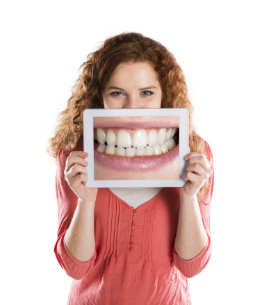 A girl holding a smile photograph on her mouth at Oregon Periodontics, P.C. in Portland, OR